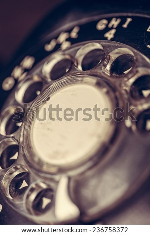 Close up of the dial on a black vintage rotary telephone with filtered effect - stock photo
