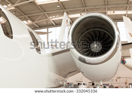 Close up of the engine housing on a small twin-engine corporate passenger jet parked in a hangar at an airport - stock photo