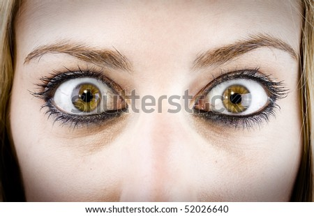 close up of the eyes of a pretty young girl in a surprise or fear expression - stock photo