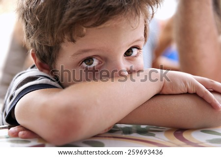 Close-up of the face of a child, with the crossed arms, looking at the camera - stock photo