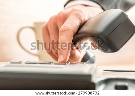Close up of the fingers of a business adviser dialing out on a land line telephone pressing the number keys on the keypad in a communications concept. - stock photo