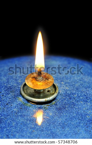 Close up of the flame of an oil lamp, on a black background. Space for text on the background.