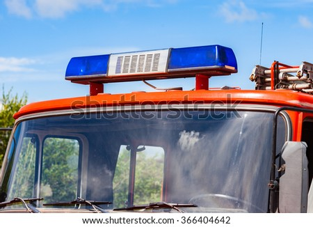Close-up of the Flashing Blue Siren Light on roof of red firetruck - stock photo