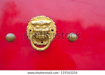 Close up of the gold knocker on the red door.