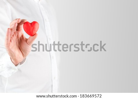 Close up of the had of a man in a white shirt holding a small red Valentines heart between his fingers showing his love for a sweetheart or loved one, with copyspace. - stock photo
