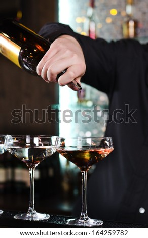 Close up of the hand of a bartender mixing alcoholic cocktails pouring from a bottle into an elegant cocktail glass on a bar counter - stock photo