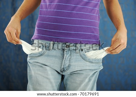 close-up of the hand of a man showing the pocket of his pants empty - stock photo
