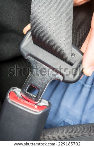 Close up of the hand of a person fastening a seatbelt in a car showing the insertion of the metal clip for safe driving and transport of passengers. - stock photo