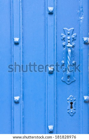 Close up of the handle and keyhole of an antique blue door
