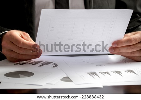 Close up of the hands of a businessman seated at his desk analysing a set of graphs and holding a spreadsheet with statistics in his hand. - stock photo