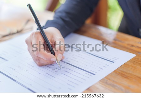 Close up of the hands of a businesswoman in a suit signing or writing a document on a sheet of white paper - stock photo