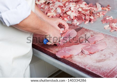 Close-up of the hands of a butcher slicing steaks with a large knife from a large piece of fresh meat over a cutting-board on top of a stainless steel workbench
