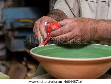 Close-up of the hands of a ceramist painting a dish onto his potter wheel