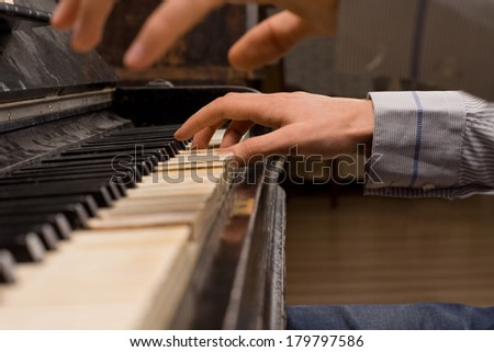 Close up of the hands of a concert pianist playing the piano striking chords as he plays a classical tune - stock photo