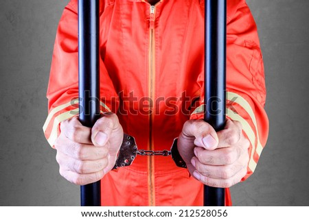 close up of the hands of a prisoners in jail with handcuffs  - stock photo