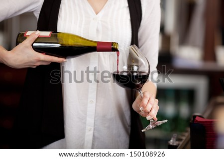 Close up of the hands of a young woman pouring red wine into a glass from a bottle - stock photo