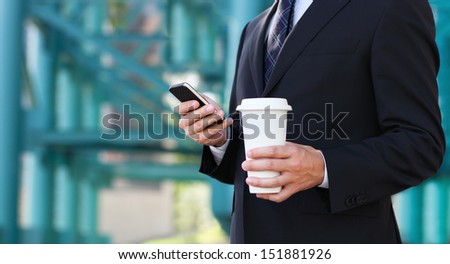 Close up of the hands of the businessman with a mobile phone and cup of a coffee. Outdoors - stock photo