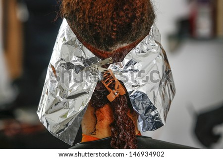 Close-up of the head of a woman in the process of getting her hair dyed by her beautician