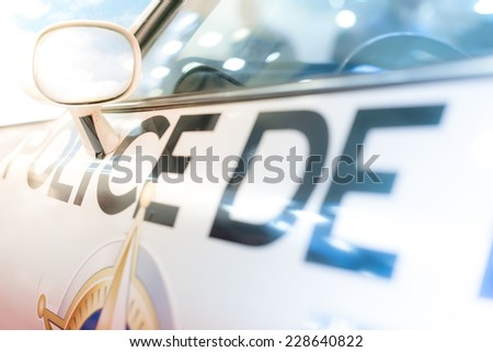 "Close-up of the left driver's door, window and side mirror of police car. There is inscription ""Police"" on door. Lights are reflected of clean car surface. - stock photo"
