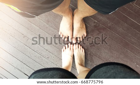 Close up of The Lover' foots ,  Male and Female happy in  love couple  standing on the wood at sunset in relax vacation