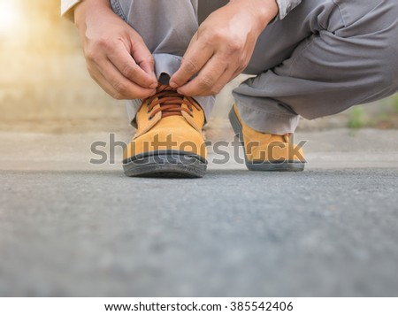 Close up of The man wears safety shoes on street with green light sun flare