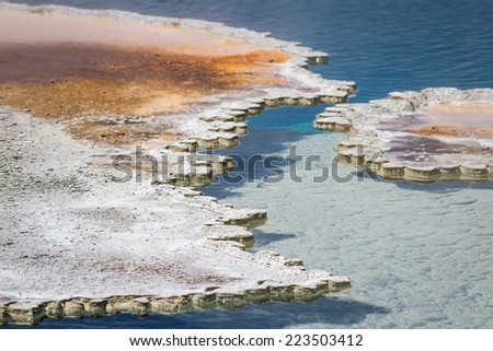 close up of the minerals forming a shell over the vibrant blue waters near a geyser
