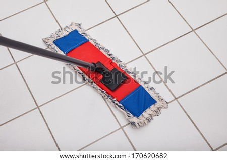 Close-up Of The Mop Washing The Tile Floor - stock photo