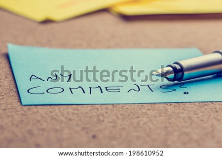 Close up of the nib of a fountain pen lying on a sheet of blue post it with words Any comments written on it, retro effect faded look. - stock photo