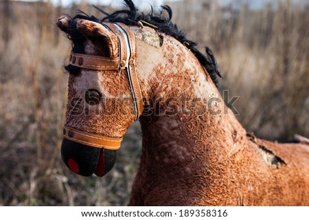 Close-up of the old threadbare rocking horse thrown away to the dump in the field - stock photo