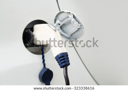 Close-up Of The Power Supply Cable Plugged Into An Electric Car - stock photo
