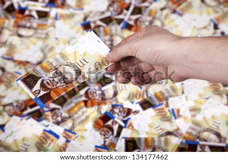 Close up of the right hand of an adult man holding a 100 NIS (New Israeli Shekel) money note, in the gesture of giving, over a defocused background of a large amount of identical bills. - stock photo