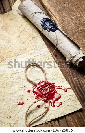 Close-up of the scroll and old paper with red sealant - stock photo