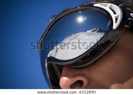 Close up of the ski goggles of a man with the reflection of the snowed mountains on its cristals - stock photo
