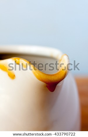 Close-up of the spout of a gravy boat with gravy dripping down