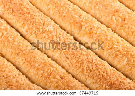 Close up of the texture of bread sticks topped with cheese