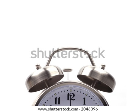 Close up of the top half of an alarm clock with the hand on twelve. The little hammer is blurred from the motion of hitting the bells.