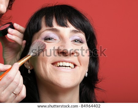 Close up of the woman paints face with makeup - stock photo