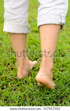 Close up of the woman walking on green grass for healthy - stock photo