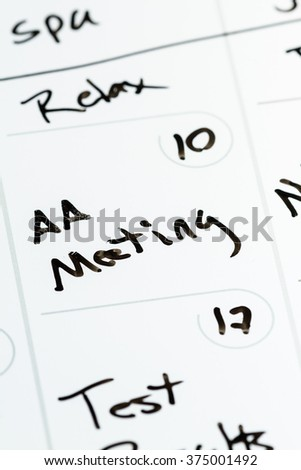 close up of the words AA meeting hand written on a calendar as a concept - stock photo