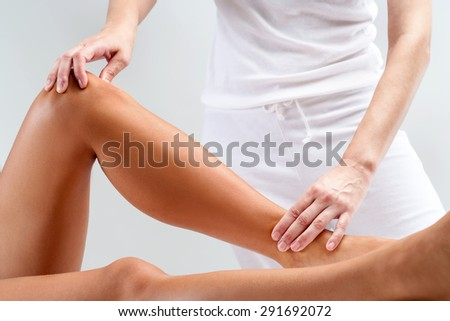 Close up of therapist doing manipulative healing treatment on female legs. - stock photo