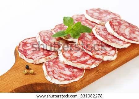 close up of thin slices of french dry salami on wooden cutting board