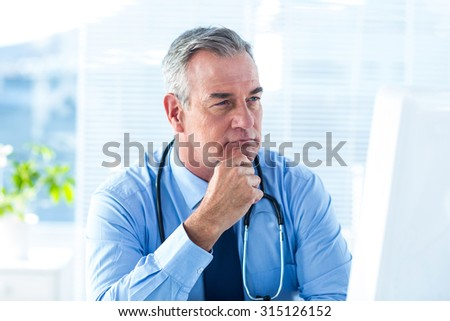 Close-up of thoughtful male doctor sitting in hospital