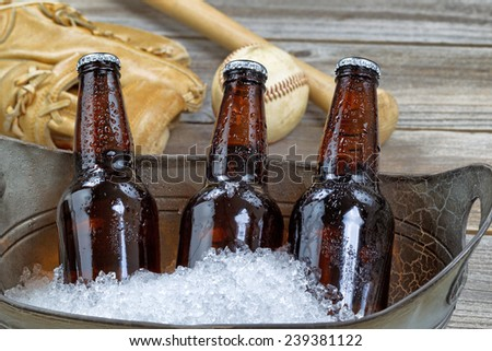 Close up of three brown cold bottled beers, crushed ice in metal container, and baseball equipment in background on rustic wood - stock photo