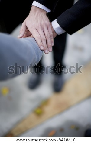 close-up of three business men's hands on top of each other
