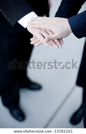 close up of three businesspeople placing hands on one another