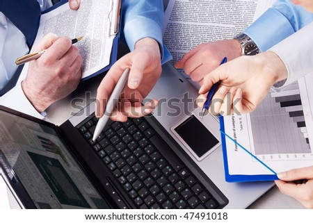 Close-up of three hands pointing at desktop - stock photo