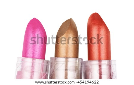 Close up of three lipsticks in different colors isolated on white