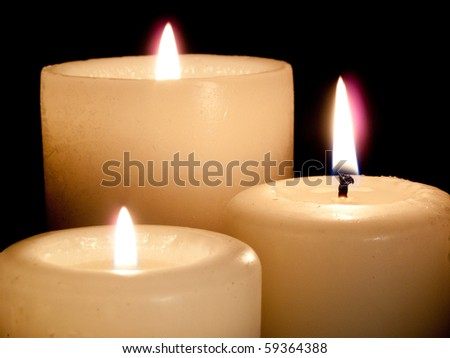 Close up of three lit white candles on black background. - stock photo