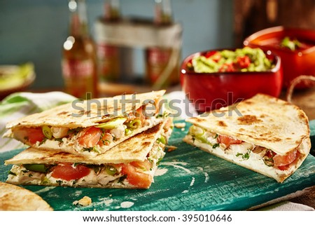 Close up of three of cooked cheese quesadillas on green cutting board with salsa and bottles in background - stock photo