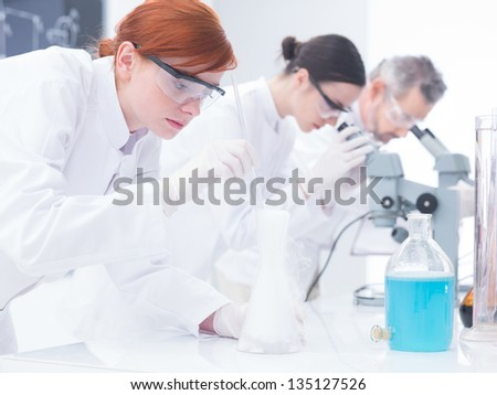 close-up of three people in a chemistry lab conducting chemical experiments on a lab table with lab tools and colorful liquids - stock photo